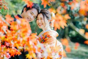 紅葉の前で笑顔のお二人