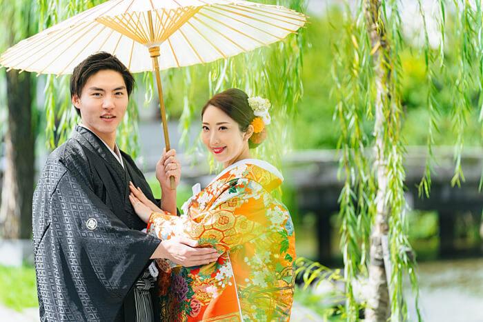 鮮やかな緑の中で和傘を使ったポーズ